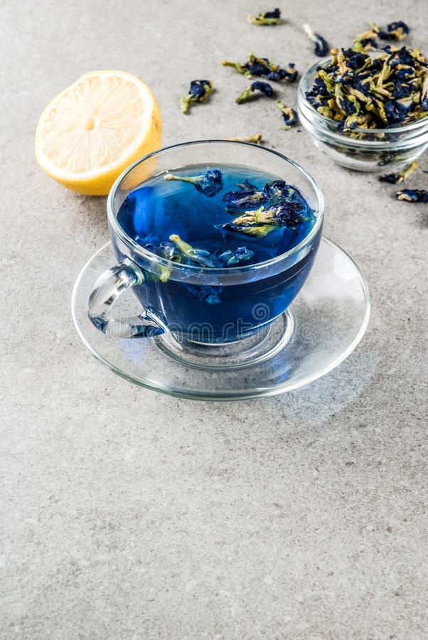 Blue butterfly pea flower tea. Healthy drinks, organic blue butterfly pea flower tea with limes and lemons, grey concrete background copy space stock photo