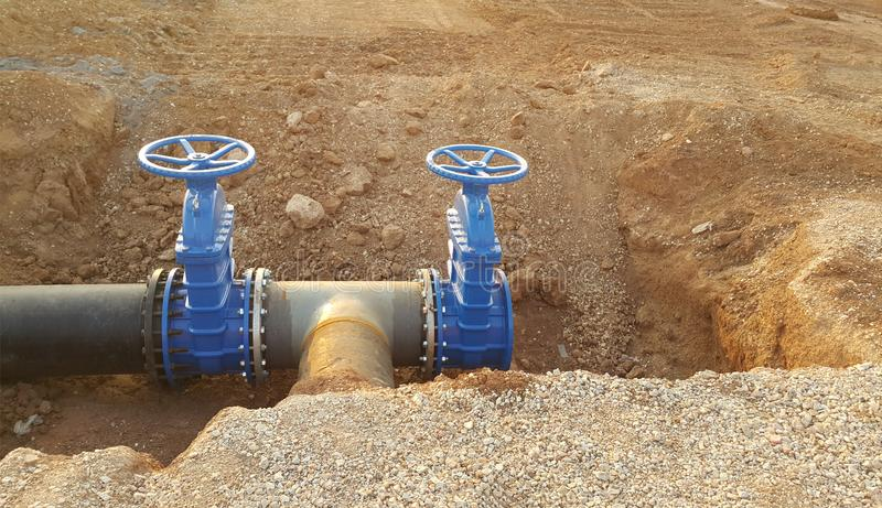 Blue butterfly valve on floor and PE. black pipe. For raw water pump stock photography