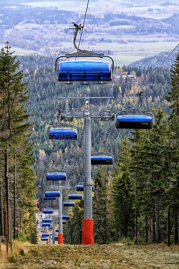 Blue cabins of ski funicular from behind. On the steep hill out of season royalty free stock image