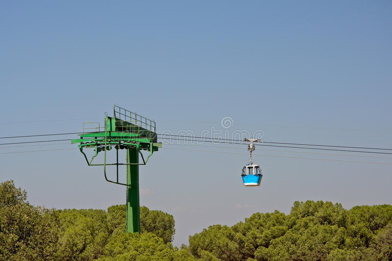 Blue cable car cabin and pillar above trees royalty free stock photos