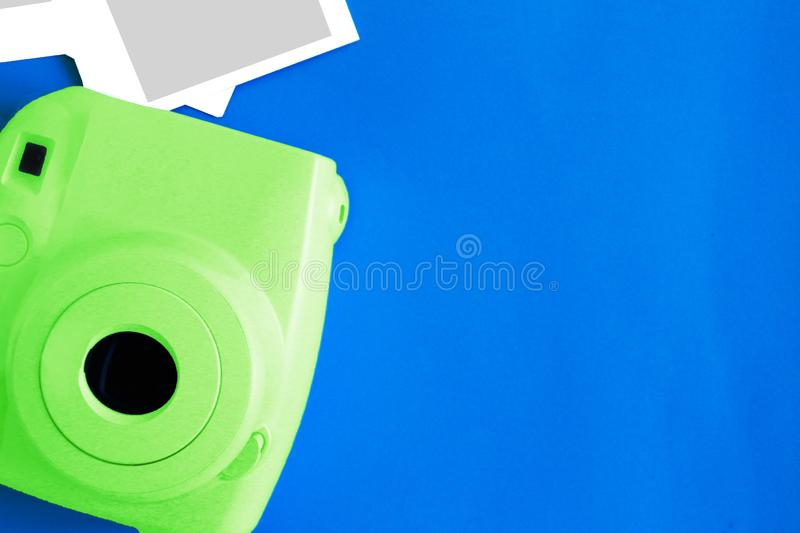 Blue camera with blank picture frames on colourful background. Fashion Film Camera. Nostalgia photography. Top view. Minimal and m stock photography