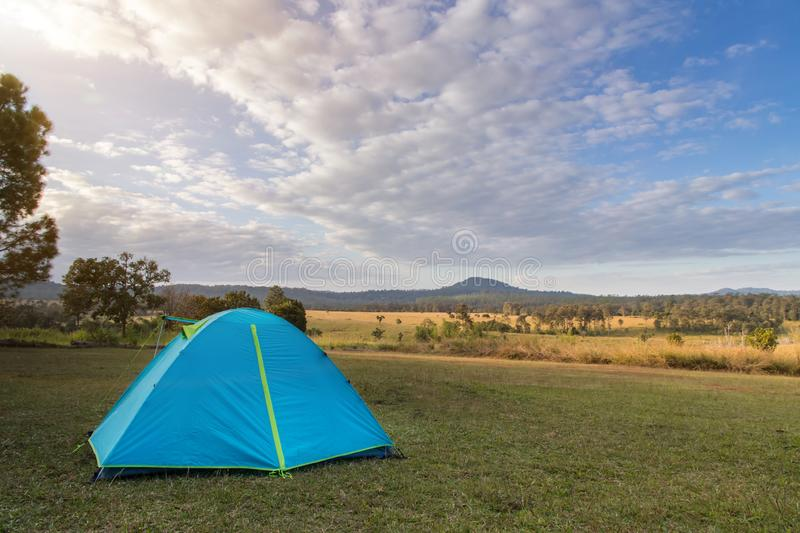 Blue camping tent on green field near forest during dramatic sunrise at summer misty morning,Concept of outdoor camping adventure stock image
