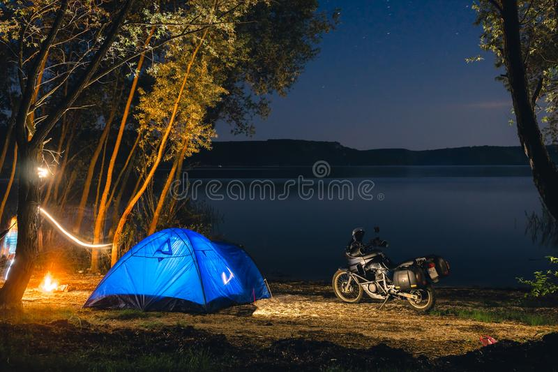 Blue Camping Tent Illuminated Inside. Night Hours Campsite. Recreation. Motorcycle traveler, tourist bikers. lake and stars. take. A rest after long riding royalty free stock photo