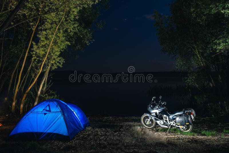 Blue Camping Tent Illuminated Inside. Night Hours Campsite. Recreation. Motorcycle traveler, tourist bikers. lake and stars. take. A rest after long riding stock photos