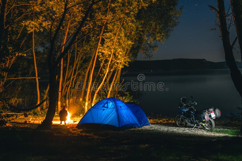 Blue Camping Tent Illuminated Inside. Night Hours Campsite. Recreation. Motorcycle traveler, tourist bikers. lake and stars. take. A rest after long riding royalty free stock photos