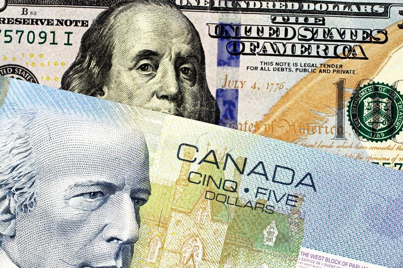 A blue Canadian five dollar bill with an American one hundred dollar bill. A close up image of a blue Canadian five dollar bill with an American one hundred stock images
