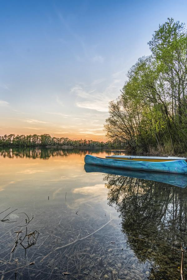 Blue Canoe on Water Beside Trees royalty free stock photos