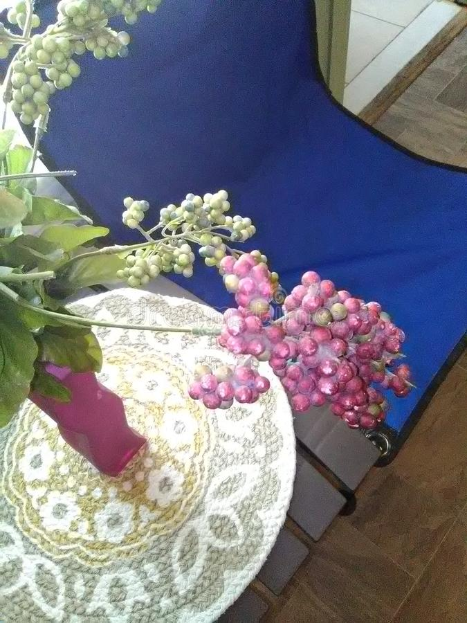 Blue canvas chair next to table covered with woven mat and vase. royalty free stock images