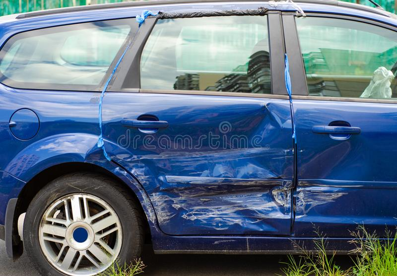 Blue car dent in a door royalty free stock image