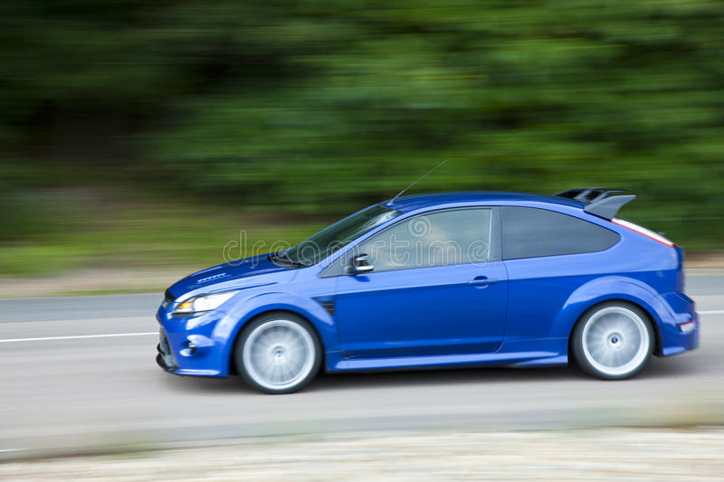 Blue car driving fast on country road. A blue car driving fast on country road stock image