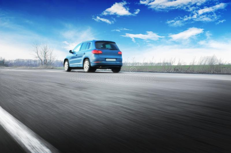 A blue car driving fast on the countryside road against sky with. A blue crossover car driving fast on the countryside asphalt road against blue sky with white stock photography