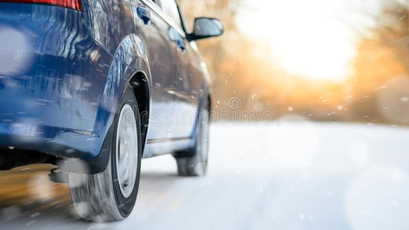 Blue Car Moving Fast on the Winter Snowy Road. Safe Driving Concept. Blue Car Moving Fast on the Winter Snowy Road. Motion Blur and Snowflakes. Drive Safe stock photos