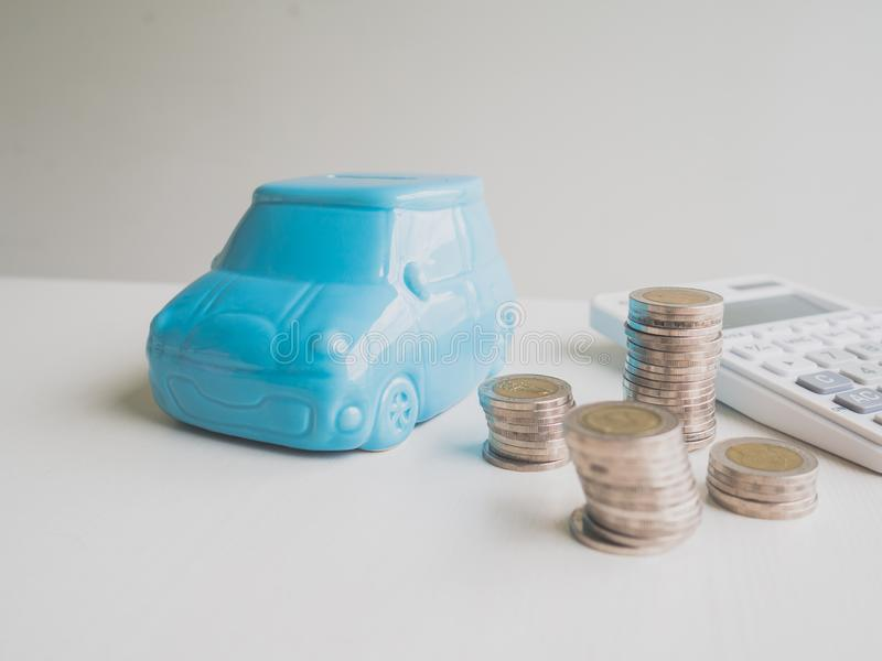 Blue car Piggy bank and calculator  with coins pile, Saving money for future plan and retirement fund concept.  royalty free stock photo