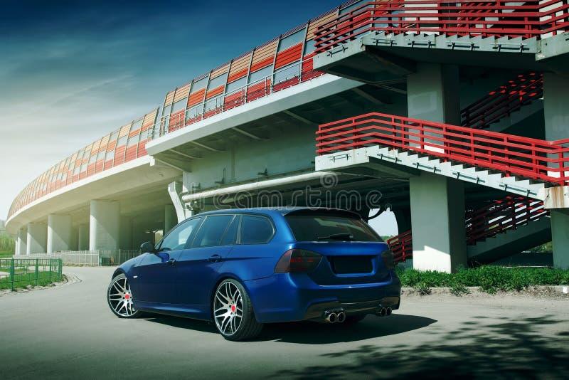 Синий автомобиль остается на асфальтированной дороге в городе. В дневное время стоковые изображения