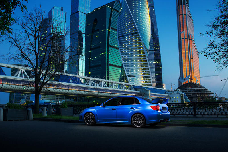 Blue car stay on road near Moscow-City at twilight royalty free stock photography