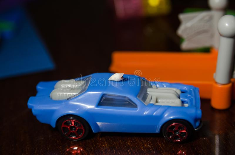 A blue car toy. A little blue car toy on wooden table backround. A toy for kids close up stock images