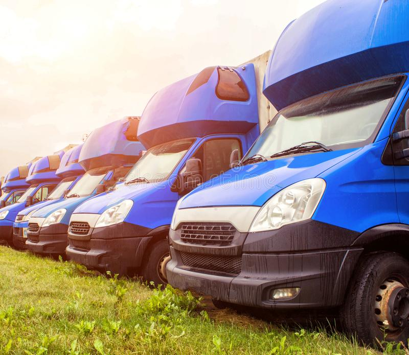 Blue cargo vans stand in a row, trucking and long-distance, trucking industry and sun. Automobile stock photos