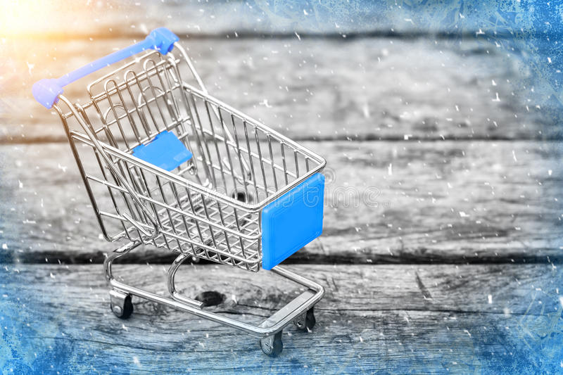 Blue cart from the grocery store on the old wooden background. New Year and Christmas buying. stock image