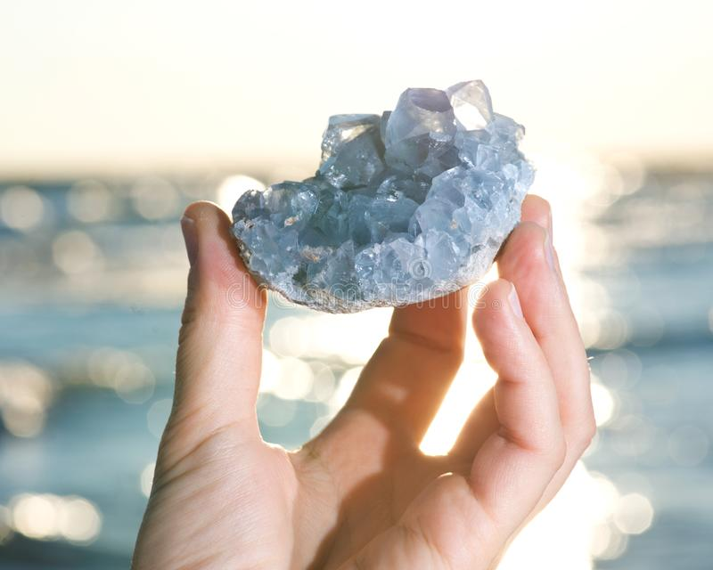 Blue Celestite cluster from Madagascar in woman`s hand at sunrise royalty free stock photos