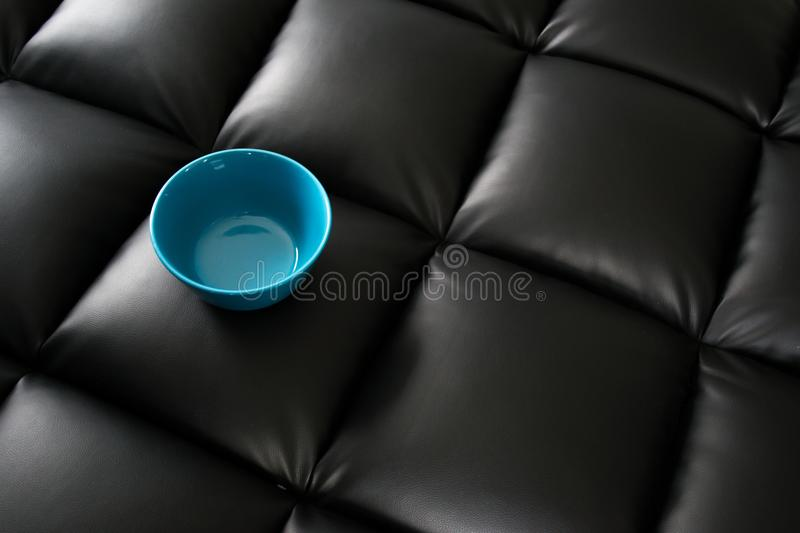 Blue Ceramic Bowl on Black Leather Surface royalty free stock photos