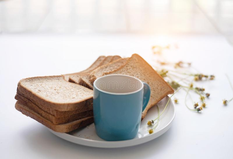 The blue ceramic coffee cup ,on white desk,with sliced bread in white dish stock photos