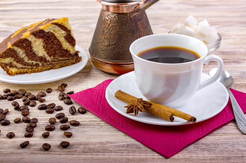 A cup of black coffee on saucer with delicious cake. White sugar cubes in a bowl, tea spoon, anise, cinnamon sticks and other acce. Blue ceramic cup of black hot stock photography