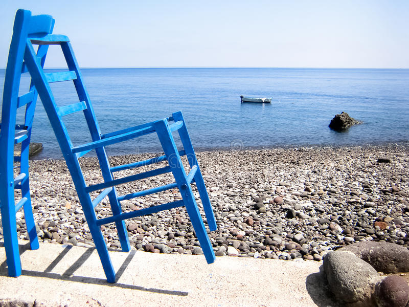 Blue chairs rocky beach royalty free stock photos