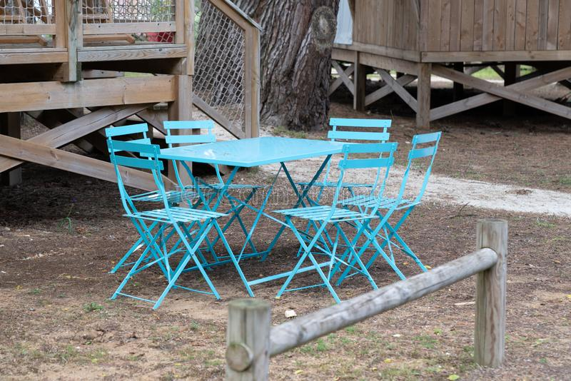 Blue chairs and table in metal outside located in the garden of wood hut house stock image