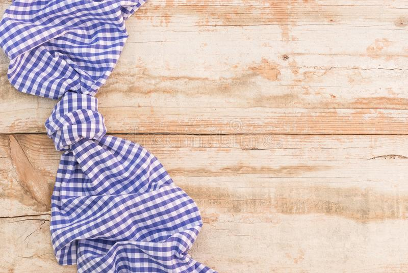 Blue checked tablecloth knotted, above old rustic wooden table surface with copy space stock photo