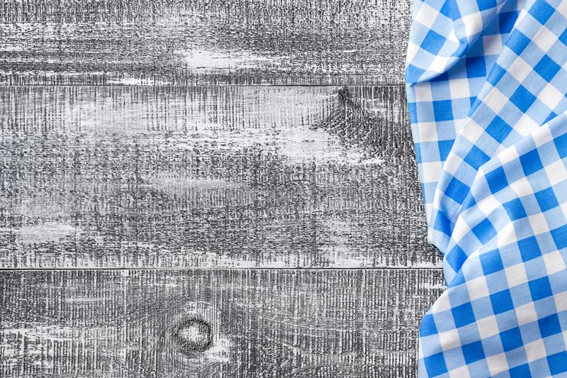 Blue checkered napkin on a gray wooden background. Top view. stock photo