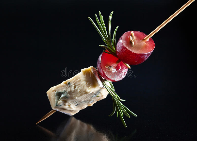 Blue cheese with grape and rosemary. On a black background royalty free stock photos
