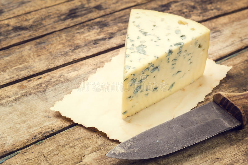 Blue cheese on old paper with rural knife. On wooden table. Warm color toned image of cheese background stock image