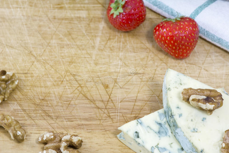 Blue cheese roquefort, strawberries and nuts royalty free stock photography