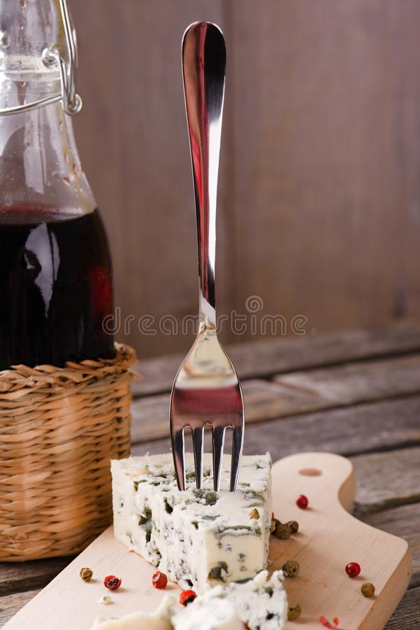 Blue cheese with single fork next to red wine stock photos