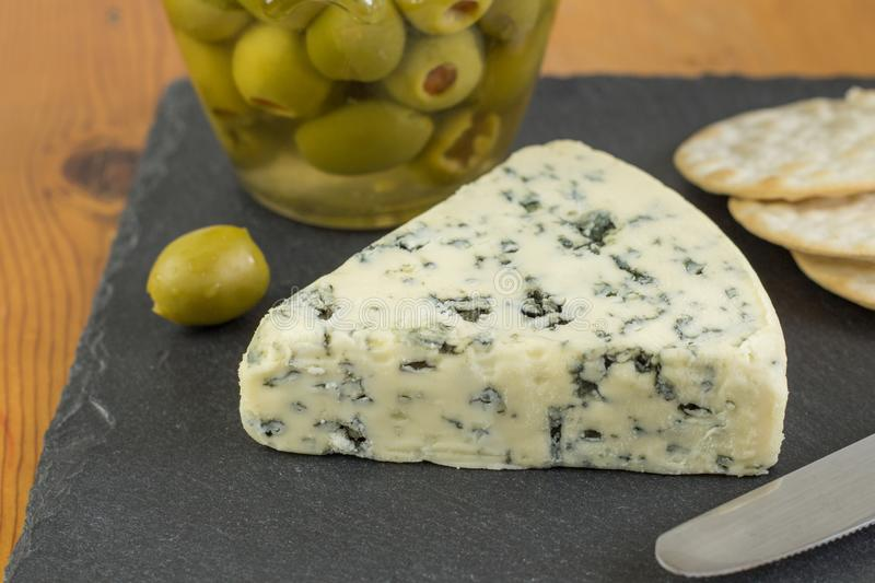 Blue cheese wedge with defocused jar of green olives and cracker stock image