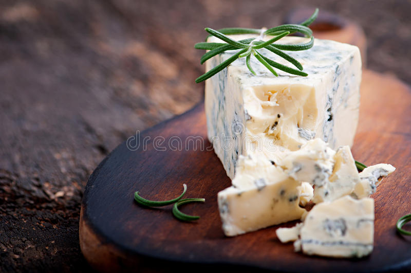 Blue cheese on the wooden background. Blue cheese on the old wooden background stock image