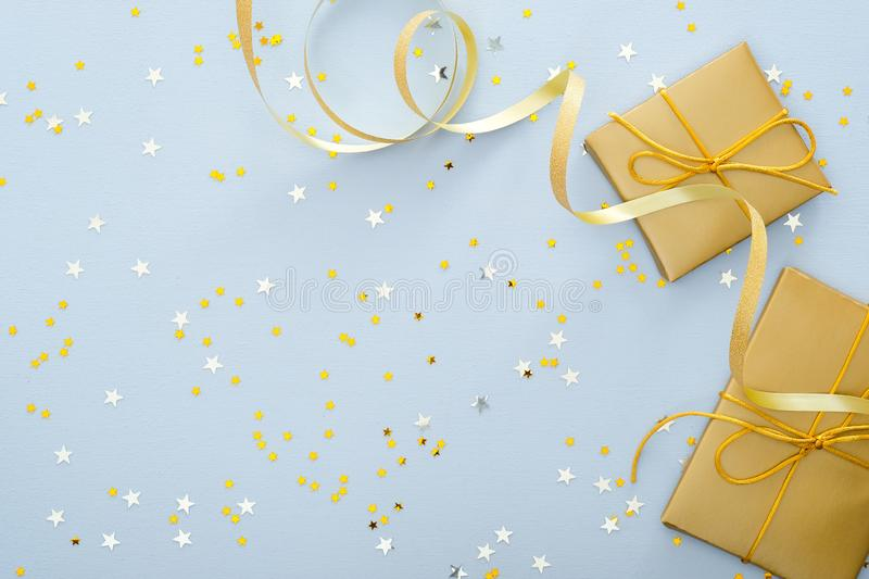 Blue Christmas background with golden gifts box, ribbon, glitter confetti stars. Christmas, New Year, winter holidays and birthday royalty free stock photos