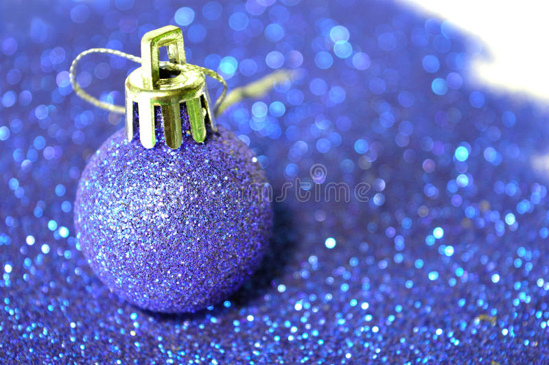 Blue Christmas ball on blurry background of blue glitter. Blue Christmas ball on background of blue glitter stock photo