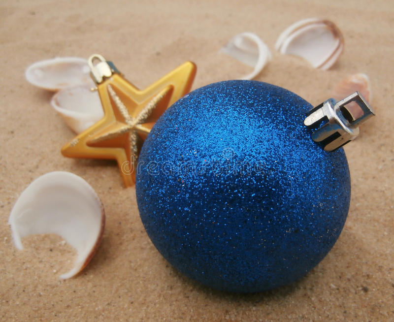 Blue christmas balls in sand royalty free stock images