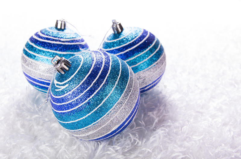 Blue christmas balls. White fur background stock image