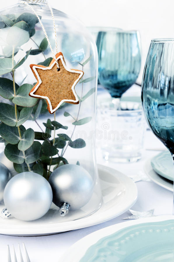 Blue christmas dinner table setting with glass dome