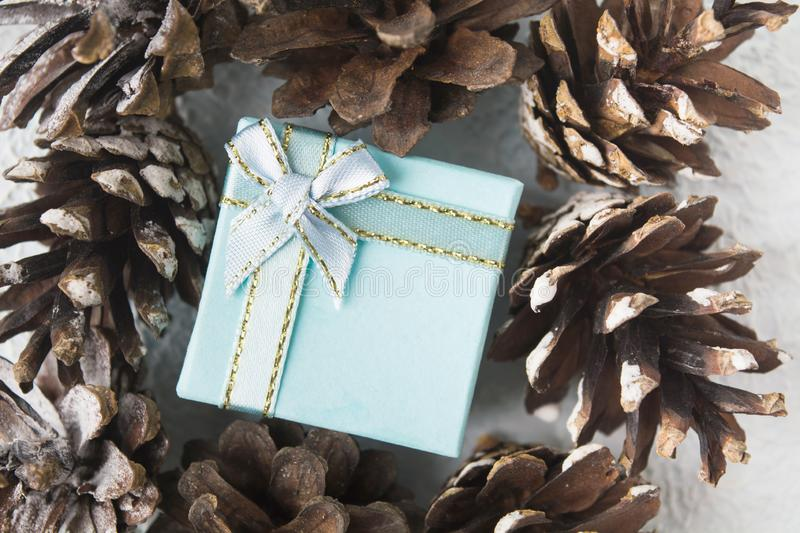 Blue Christmas gift box with pinecones, flat lay style stock images