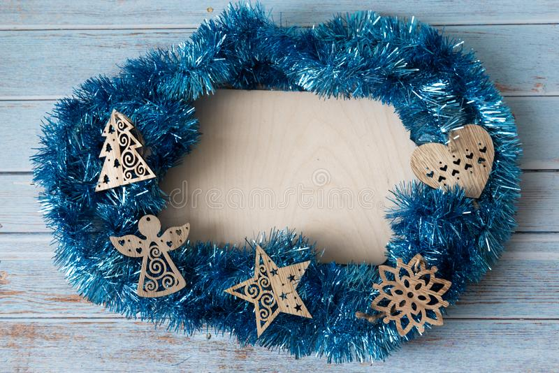 Blue Christmas tinsel surrounds a blank antique wooden tablet and blue wood background. Christmas composition with wooden toys. royalty free stock photos