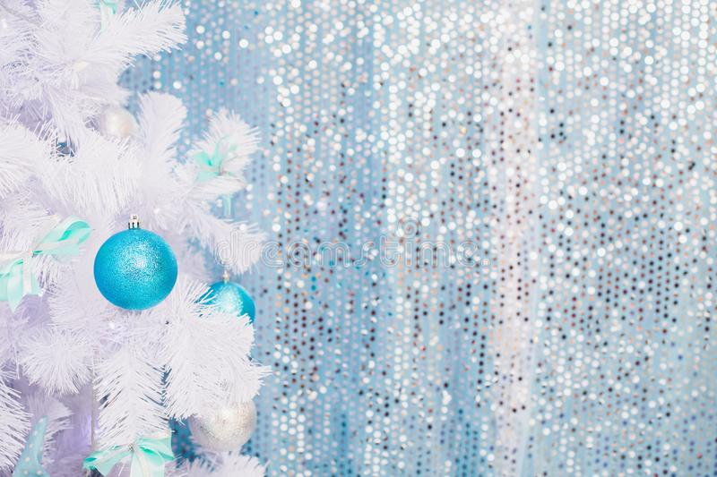 Blue Christmas toy hanging on a white spruce with snow. New Year background royalty free stock images