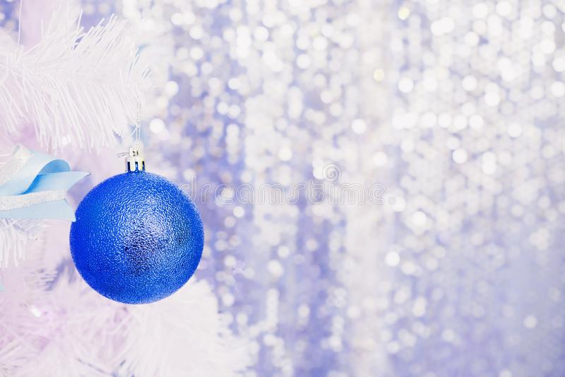 Blue Christmas toy hanging on a white spruce with snow. New Year background stock photo
