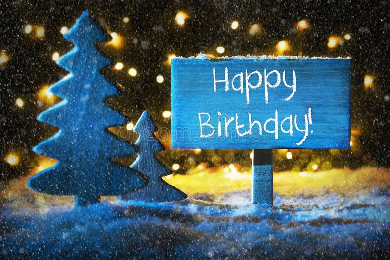 Blue Christmas Tree, Text Happy Birthday, Snowflakes. Sign With English Text Happy Birthday. Blue Christmas Tree With Snow And Magic Glowing Lights In Backround royalty free stock photos