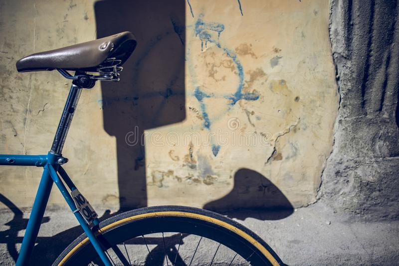 Blue city bicycle parked on a wall on a urban scene. Blue city bicycle parked on a damaged old wall on a urban scene stock photos