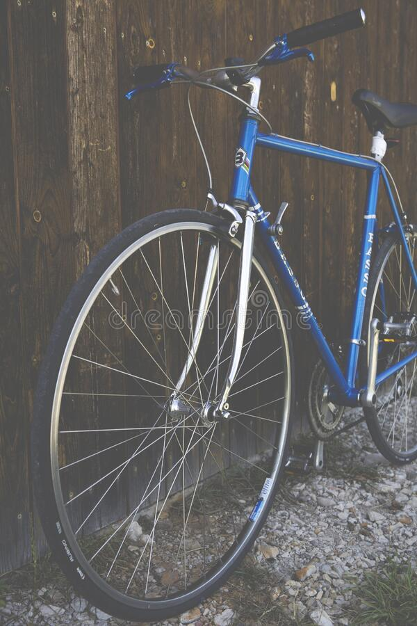 Blue City Bike Beside Brown Wooden Fence stock photo