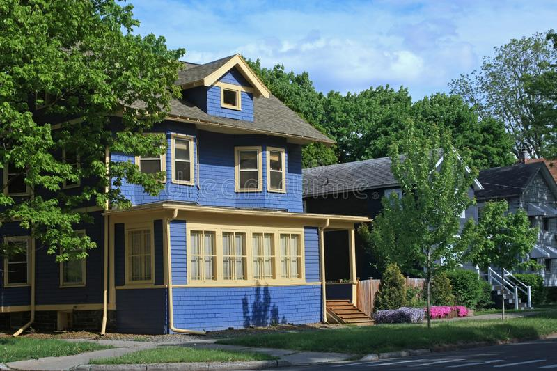 Blue clapboard house. With dormer window, on a street with similar houses royalty free stock image