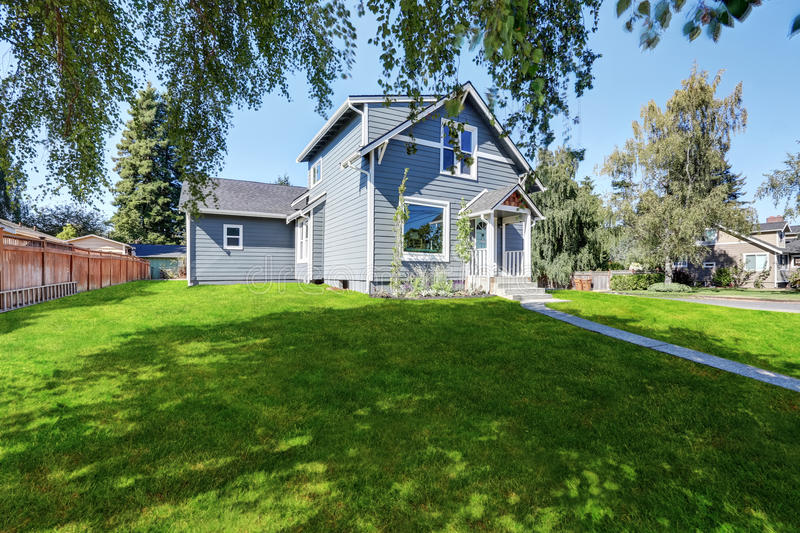Blue clapboard siding house with grass filled front yard. Northwest, USA royalty free stock photo